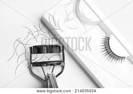 Curler and false eyelashes on white background