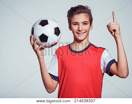 Photo of smiling teen boy in sportswear holding soccer ball and pointing  finger up - posing at studio