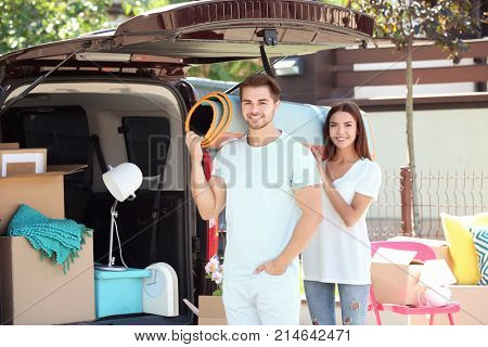 Young couple putting their belongings in car trunk outdoors