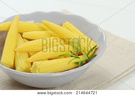 bowl of sweet baby corn on beige place mat - close up