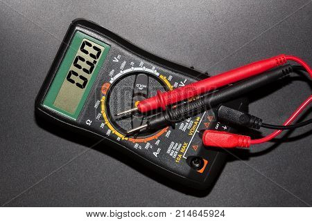 digital multimeter with probes closeup on a black background