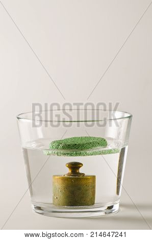 Physics. A pumice floats in water and a antique weight sinks.