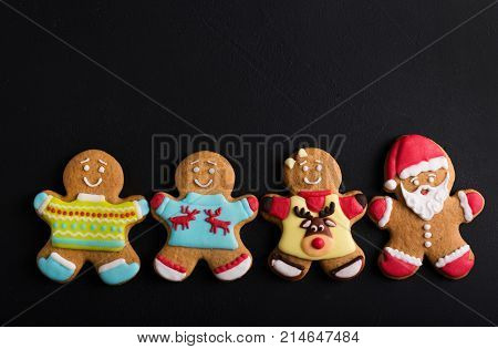 Ginger men with colored glaze on a black background . Gingerbread. Christmas cookies.