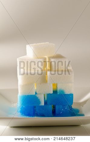 Physics. Capillary action. Dyed water is going up sugar cube tower. poster
