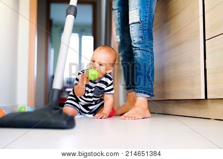 Unrecognizable young mother with a baby son doing housework. Woman hoovering and baby boy crawling on the floor. poster