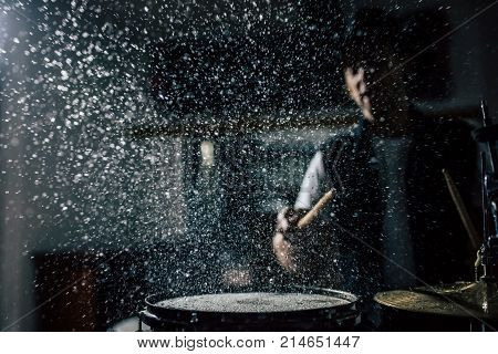 Repetition of rock music band. Drummer behind the drum set. Water splashes on snare drum. poster