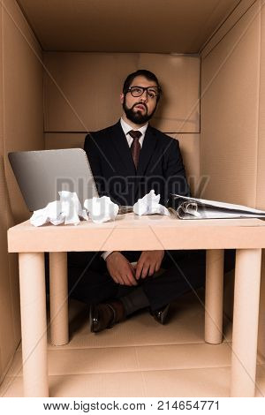 Exhausted Businessman Sitting In Box