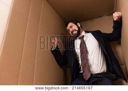 stressed businessman standing in big cardboard box