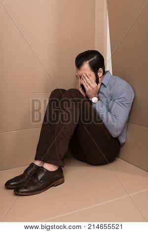 depressed man crying and sitting in big cardboard box