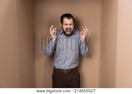 stressed man screaming in big cardboard box