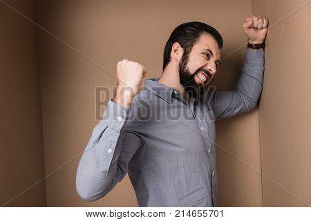 aggressive man standing in big cardboard box