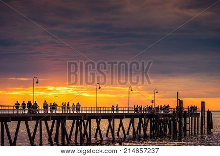 Adelaide Australia - January 19 2016: People walk along Glenelg Jetty at sunset. Jetty was opened for public on 25 April 1859 and is one of the most popular tourists attractions