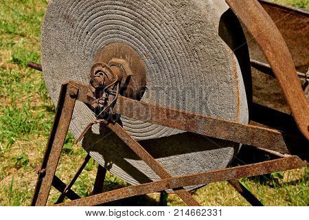 A very old grindstone for sharpening knives and axes sets in a metal frame with foot pedals.