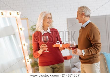 Happy anniversary darling. Joyful elderly couple exchanging gift and drinking red wine while celebrating their anniversary at home.