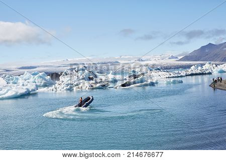 Beatufil vibrant picture of icelandic glacier and glacier lagoon with water and ice in cold blue tones, Iceland, Glacier Bay. in the lagoon a motor boat is floating