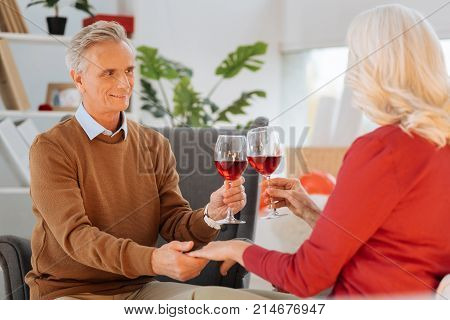 Romantic evening. Selective focus on an extremely happy retired gentleman looking at his soulmate with eyes full over while holding her hand and proposing a toast.