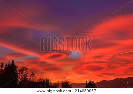 a spectacular  sunset of lenticular clouds paints the sky of orange,yellow and violet /the lenticular clouds are due to the diffusion of water vapor,the red rays of the sun crossing the crystalline atmosphere
