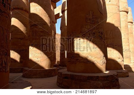 Columns covered with hieroglyphics in majestic hypostyle hall at Karnak Temple - Luxor, Egypt