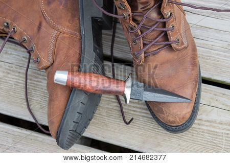 A boot knife displayed on work boots.