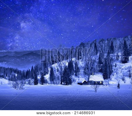 Small wooden house in a night winter mountain landscape with a beautiful starry sky at winter night landscape on a starry sky background - Christmas background