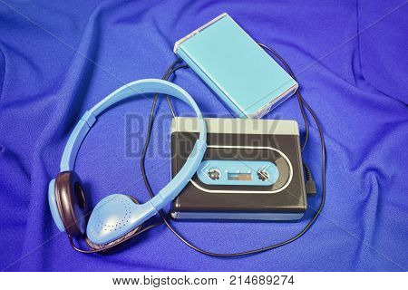 Retro walkman, headphones and cassette cover on the blue fabric background