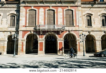 BARCELONA SPAIN - NOV 12 2017: Parliament of Catalonia - Parlament de Catalunya building on a sunny day with one male cylcist biking in front