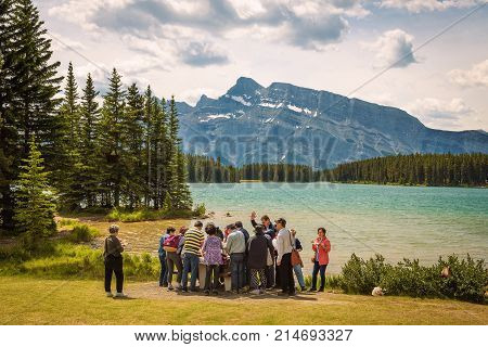 TWO JACK LAKE, ALBERTA, CANADA - JUNE 26, 2017 : Group of Asian tourists having lunch at the two jack lake in Banff National Park with Mt. Rundle in the background.