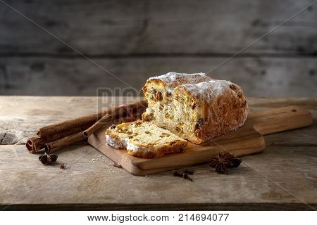 Christmas cake in germany christstollen with cinnamon sticks and anise stars on a rustic kitchen table wooden vintage background with copy space selected focus narrow depth of field