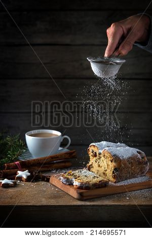 christmas cake in germany christstollen is sprinkled with icing sugar coffee cup spices and cinnamon star cookies on a rustic wooden table dark vintage background with copy space vertical selected focus