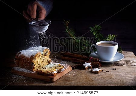 christmas cake in germany christstollen and sprinkling powdered sugar from a sieve in a woman hand coffee cup spices and cinnamon star cookies on a rustic wooden table dark vintage background with copy space selected focus