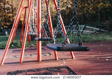 Close up of a row of emplty swings in a park on a summy autumn day
