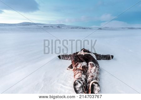 Russia, Siberia, Yamal. Lying in the snow man in Nenets warm clothes. At a cold temperature