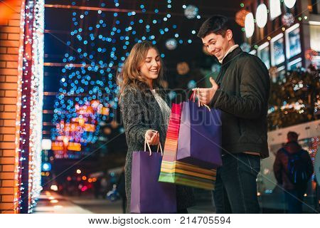 The happy couple with shopping bags enjoying night at city background and walking with shopping bags. Lifestyle.