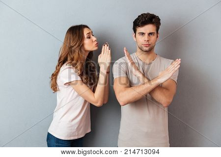 Portrait of a young casual couple standing together isolated over gray wall background, woman asking for something and man showing crossed hands