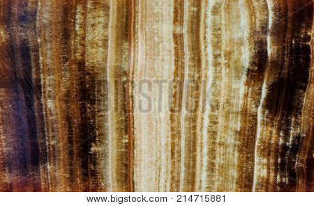 Marbled Onyx mineral stone pattern texture macro view. Beautiful brown color background layered chalcedony variety of quartz gem.