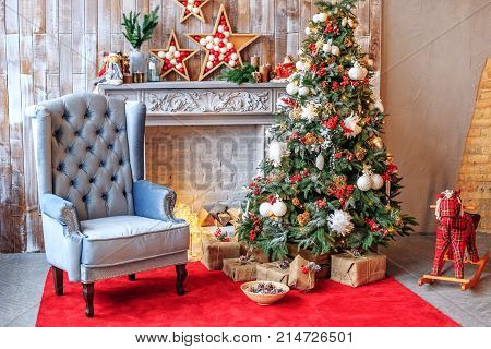 The unusual interior of the living room in the loft is decorated with a Christmas tree. Concept of Happy Christmas New Year holiday background.
