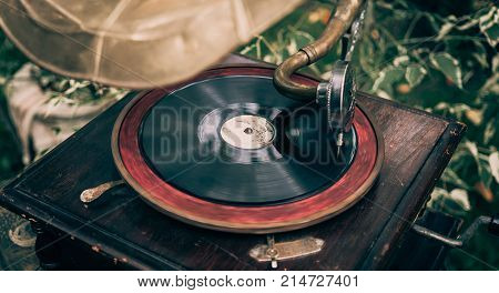 Old vintage gramophone or turntable player with disc close up, retro toned