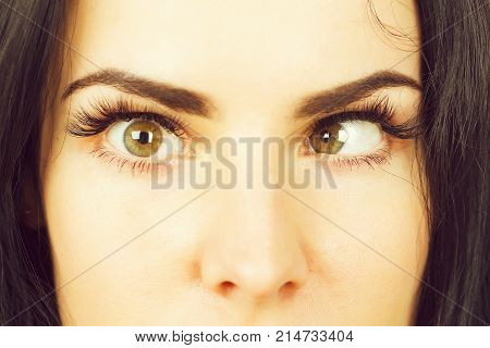 crazy female eyes with strabismus of pretty woman or cute girl at optician with mad comic or surprised face closeup