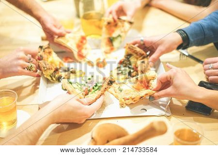 Close up of people hands taking diverse slices of delicious italian pizza at home - Group of friends enjoying a meal eating take away food and drinking beers - Concept of friendship. lifestyle lunch