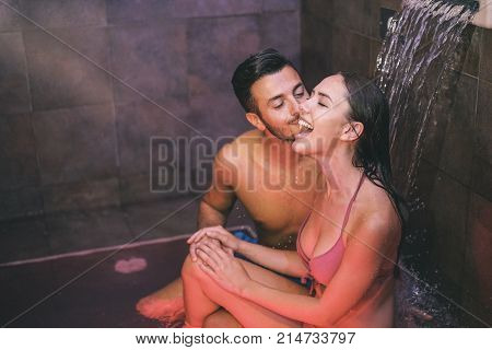 Young couple of lovers enjoying the pool waterfall hotel resort spa - Loving teenagers having fun and relaxing at wellness spa day - Man giving a kiss to his girlfriend - Concept of relax and love