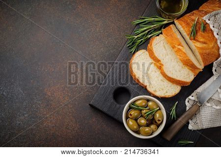 Italian traditional Ciabatta bread with olives olive oil pepper and rosemary on a dark stone or concrete background. Selective focus.Top view. Copy space.