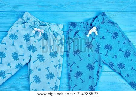 Beautiful design kids summer breeches. On sales kids casual pants pattern, blue wooden background. Children summer fashion clothing.