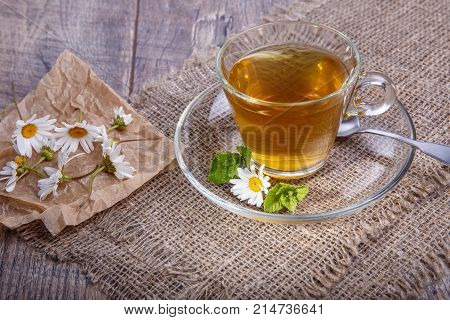 A cup of tea with chamomile on a wooden background. Alternative, traditional medicine. Healthy lifestyle