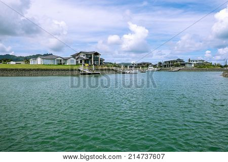 Waterfront houses with private boat jetties at Marsden Cove near Whangarei Northland New Zealand NZ - copy space in sea and sky