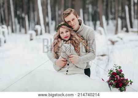 Newlyweds are hugging in the winter forest. Couple in love. Winter wedding ceremony. Artwork