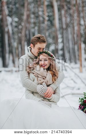 Happy newlyweds are hugging in the winter forest. Couple in love. Winter wedding ceremony. Artwork