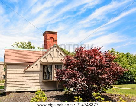 A small clapboard cottage with a large red brick chimney