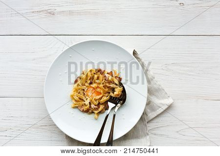 Italian restaurant food top view, carbonara pasta with bacon, egg yolk and parmesan decorated with basil on white round plate.