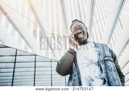 Bottom view of cheerful black dude in glasses and jean jacket standing in settings of modern skyscraper with striped ceiling and talking on the phone with copy space zone for advert or your message