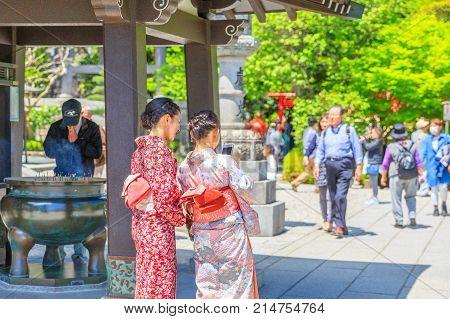 Kamakura, Japan - April 23, 2017: Japanese women wearing Japanese traditional kimono take selfie at Hase-dera in Kamakura. Hase-dera Buddhist temple is famous for housing a massive statue of Kannon.
